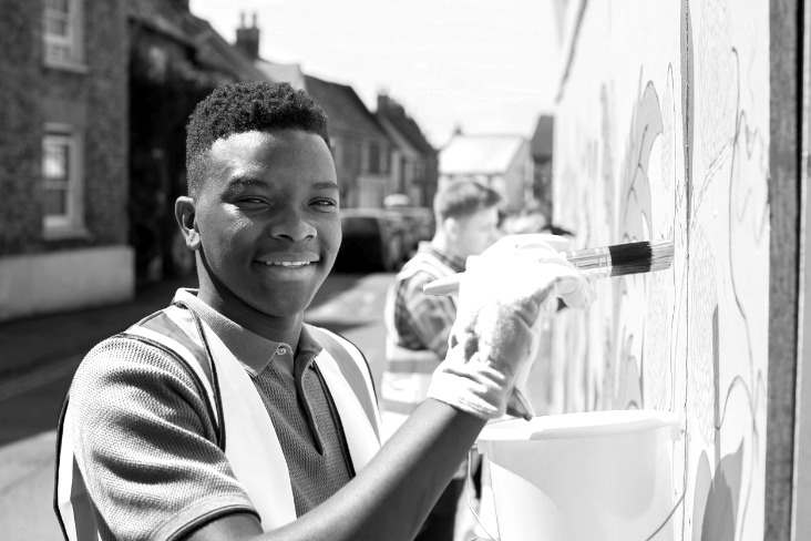 A teenage boy painting a wall as part of a community project having taken extended enterprise learning