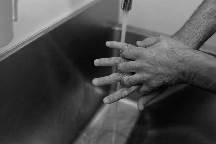 Male surgeon washing hands in a sink