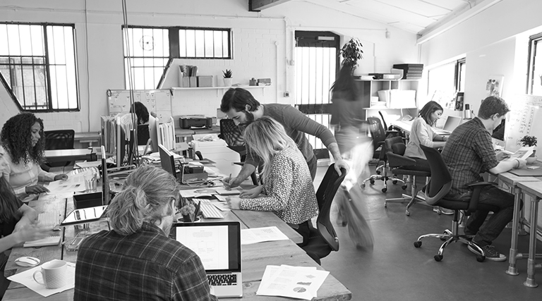 A black and white photo of a busy office with colleagues helping one another