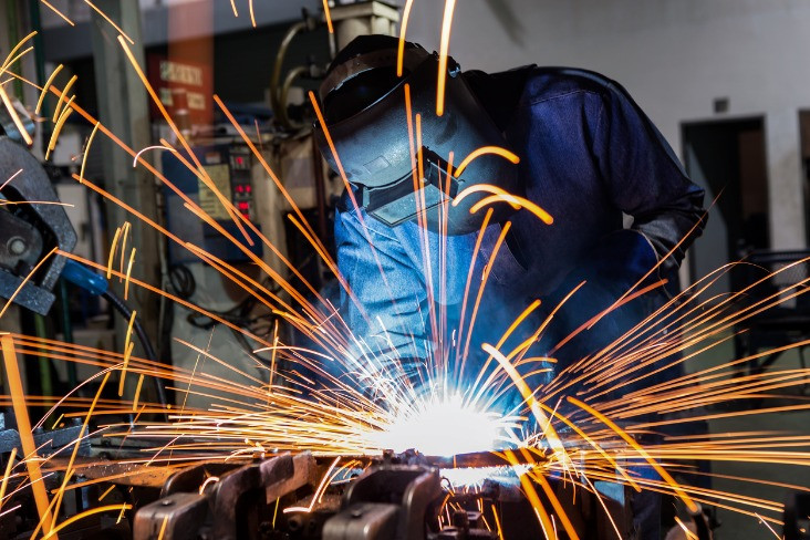 Welder adhering to compliance regulations in a factory