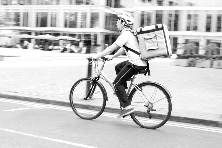 Contingent worker on bicycle delivering food
