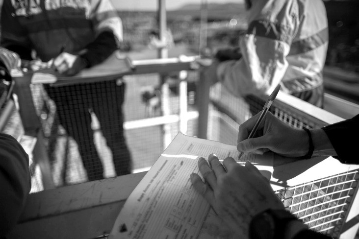 Safety supervisor reviewing a safety document on a crane