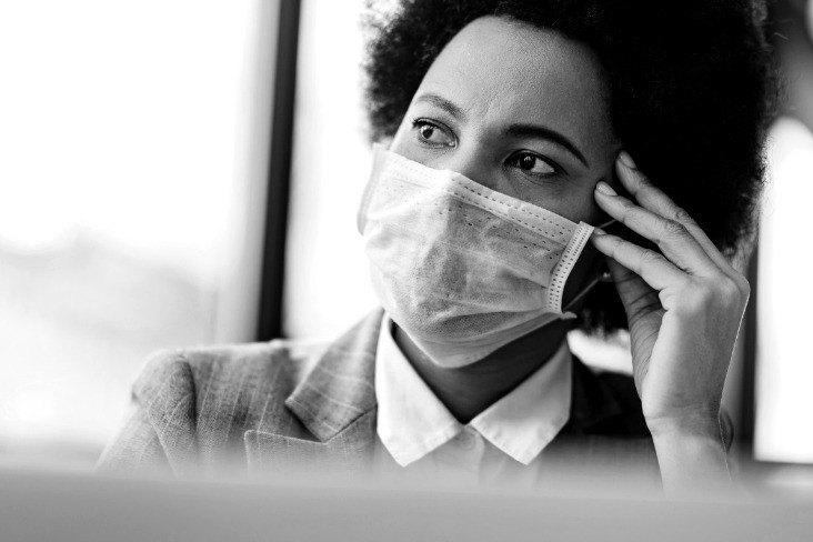 A woman wearing a face mask in an office