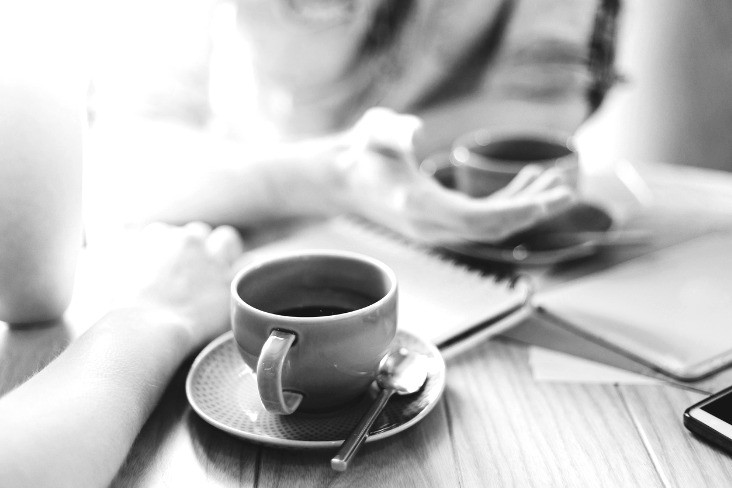 Black and white image of two colleagues talking over coffee
